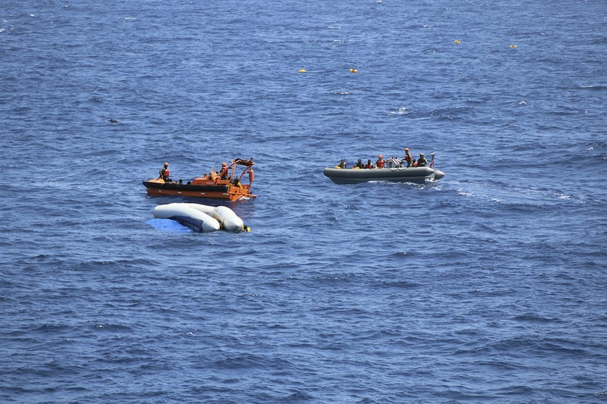 This photo made available Wednesday, June 13, 2018 sailors from the USNS Trenton rescue people from an overturned rubber dingy, in the Mediterranean Sea, Tuesday, June 12, 2018. The U.S. Sixth Fleet, which is based in Naples, Italy, said in a brief statement to The Associated Press that the USNS Trenton on Tuesday