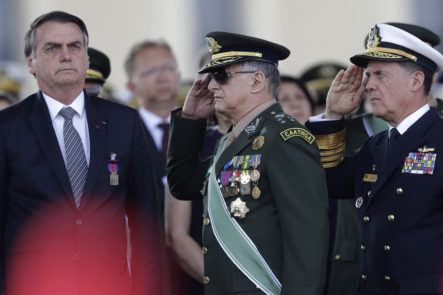 The the red kepi of military cadet in the foreground, Brazils President Jair Bolsonaro, left, receives military honors from Army Commander General Edson Leal Pujol, center, during a military ceremony for the Day of the Soldier, at Army Headquarters in Brasilia, Brazil, Friday, Aug. 23, 2019. Brazilian President Jair Bolsonaro says he's leaning toward sending the army to help fight Amazon fires that have alarmed people across the globe. (AP Photo/Eraldo Peres) Jair Bolsonaro,Edson Leal Pujol