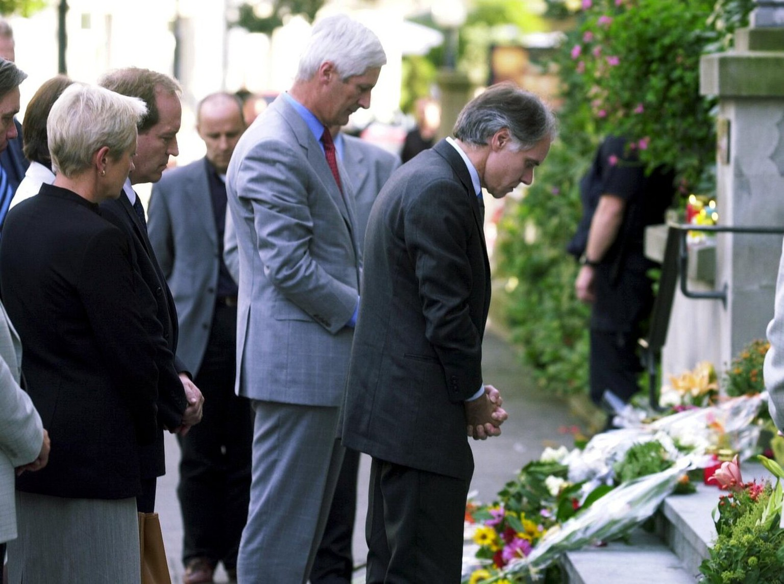 Swiss president, Moritz Leuenberger, right, und the president of the lower house of the Swiss Parliament, Peter Hess, left, have a moment of silence in front of the Parliament's building, in Zug, Switzerland, after a gunmen stormed the regional assembly and opened fire on Thursday, September 27, 2001. 15 people have been killed, including 3 members of government, 11 members of regional parliament and the gunman himself. Police identified the attacker as Friedrich Leibacher, a 57-year-old Swiss from the canton of Zurich. (KEYSTONE/Walter Bieri)