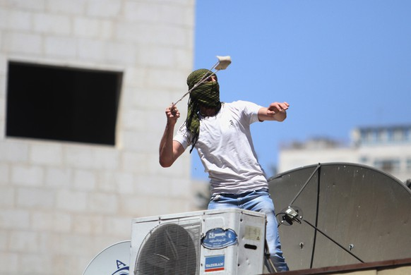 A Palestinian protester hurl a stone at Israeli soldiers during clashes, following a protest against the Israeli military action in Gaza, in the West Bank city of Hebron, Friday, Aug. 1, 2014. (AP Photo/Nasser Shiyoukhi)