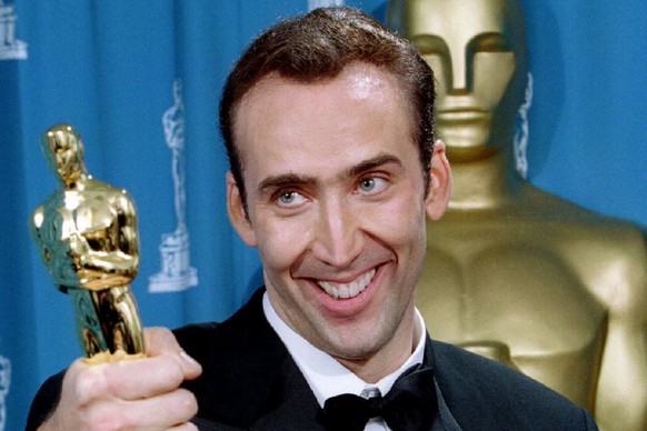 Actor Nicolas Cage gives holds his Oscar statuette after winning an Academy Award as best actor for his role in