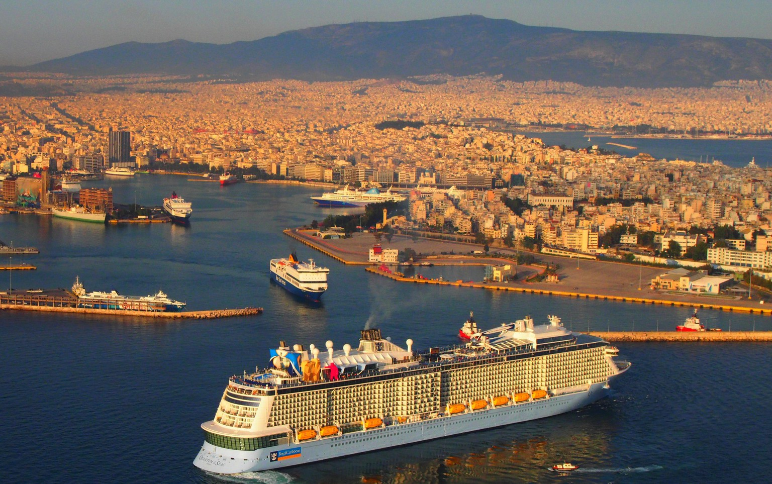 epa04755853 An aerial view shows the 347-meter long cruise ship Quantum of the Seas (F) of Royal Carribean as it enters the port of Piraeus near Athens, Greece, 18 May, 2015. Speaking at the 19th Economist Roundtable in Athens on Friday, Alternate Minister for Tourism Elena Kountoura said that an extension of the tourist season is still the target for Greece, as well as to make the 'top five; for the world's most popular destinations.  EPA/GEORGE CHRISTAKIS