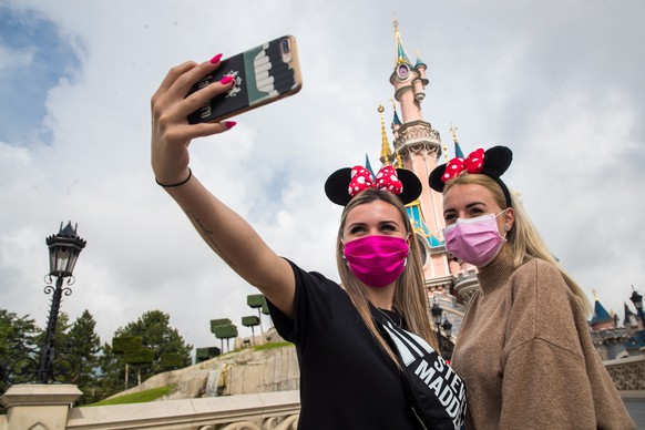 epa08547272 Visitors wearing protective face masks take a selfie picture in front of the Sleeping Beauty Castle for the official reopening of the Disneyland Paris theme park in Marne-la-Vallee, near Paris, France, 15 July 2020. Disneyland Paris closed on 15 March 2020 due to the coronavirus disease (COVID-19) outbreak.  EPA/CHRISTOPHE PETIT TESSON