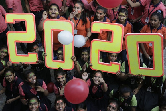 Indian school children pose for the cameras during an event to welcome the New Year in Ahmadabad, India, Tuesday, Dec. 31, 2019. (AP Photo/Ajit Solanki)