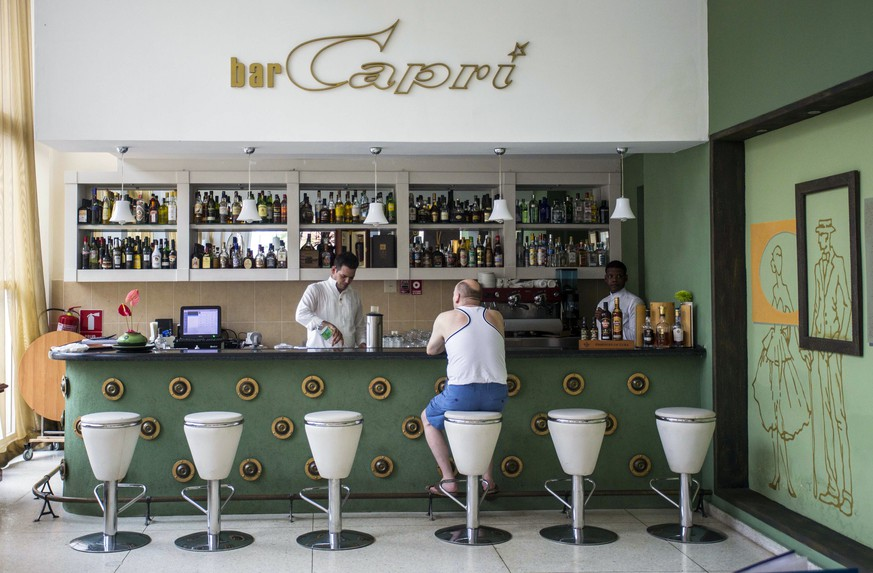 "In this Sept. 12, 2017, photo, a customer sits at the lobby bar of the Hotel Capri in Havana, Cuba. New details about a string of mysterious ""health attacks"" on U.S. diplomats in Cuba indicate the incidents were narrowly confined within specific rooms or parts of rooms. Aside from their homes, officials said Americans were attacked in at least one hotel, the recently renovated Hotel Capri, steps from the Malecon, Havana's iconic, waterside promenade. (AP Photo/Desmond Boylan)"
