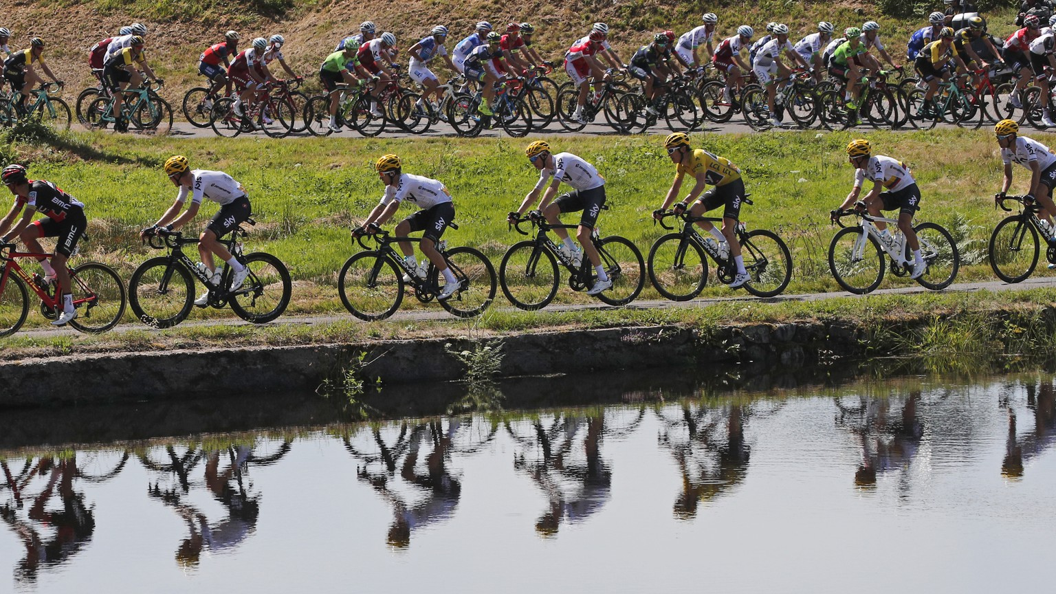 FILE - In this July 5, 2017 file photo, the pack with Britain's Geraint Thomas, wearing the overall leader's yellow jersey, is reflected in a pond during the fifth stage of the Tour de France cycling race over 160.5 kilometers (99.7 miles) with start in Vittel and finish in La Planche des Belles Filles, France. With seven mountain stages and five summit finishes, including three above 2,000 meters, this year's Tour de France is the highest in the history of the race. (AP Photo/Christophe Ena, File)