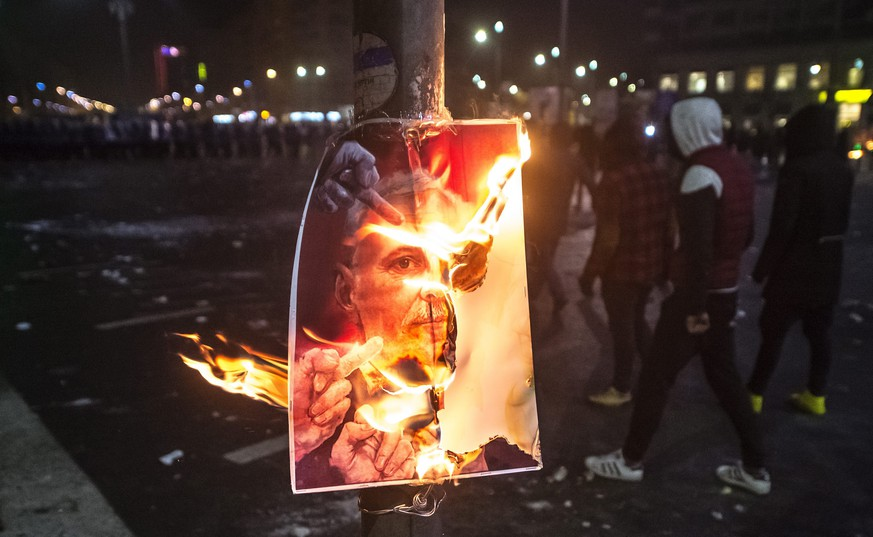 epa05765724 Masked protesters pass a burning poster during a protest rally in front of government headquarters in Bucharest, Romania, early 02 February 2017. Up to 100,000 people gathered peacefully in front of the government building and blocked the city traffic to protest against a government bill, that passed through during a government session on the evening of 31 January, as a government ordinance to pardon those sentenced to jail terms shorter than five years. According to media reports, the protests took a violent turn when a few hundred allegedly soccer supporters provoked riot police with stones, flares and firecrackers, to which the riot police responded with tear gas and arrests.  EPA/ALEX DOBRE