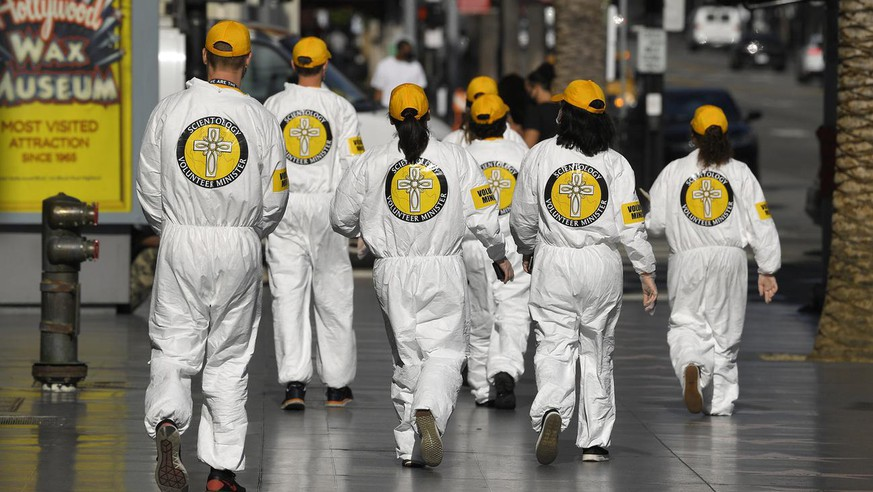 People wearing Scientology Volunteer Ministries logos walk near Hollywood and Highland during the coronavirus outbreak Thursday, May 14, 2020, in the Hollywood section of Los Angeles. (AP Photo/Mark J. Terrill)