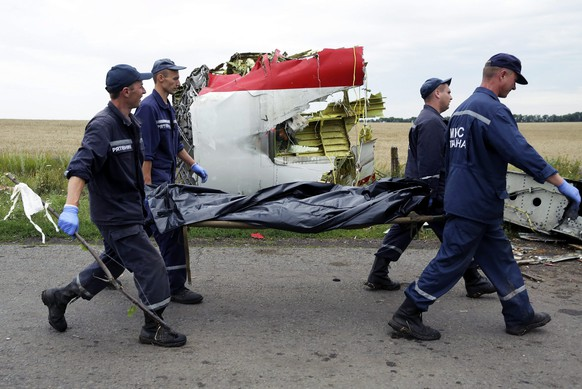 epa04392083 (FILE)( A file picture dated 19 July 2014 shows rescue forces carrying bodies of passengers at the MH17 crash site of Boeing 777, Malaysia Arilines flight MH17 airplane, in the eastern Ukraine region near Donetsk, Ukraine. Malaysia Airlines Flight MH17 crashed after breaking up in the air probably after being hit 'by a large number of high-energy objects,' a preliminary Dutch investigative report released on 09 September 2014 finds. Images of the MH17 wreckage show that it was pierced in numerous places from the outside, causing the Boeing 777 to break up in flight over eastern Ukraine, the preliminary Dutch investigative report says. Investigators found no evidence that the crash resulted from a technical problem or crew error, says the report by the Dutch Safety Board.  EPA/ANASTASIA VLASOVA *** Local Caption *** 51487745