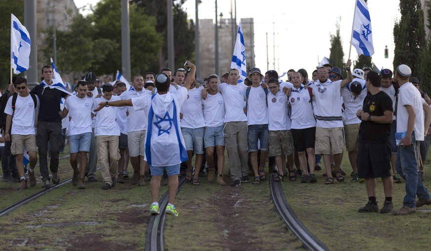 epa04753968 Israelis marching down the Light Rail tram tracks outside the Old City walls as they approach the Damascus Gate area in East Jerusalem in order to march into the Moslem Quarter of Jerusalem's Old City on 'Jerusalem Day,' 17 May 2015. The final destination for thousands of marchers, mostly right-wing Jews and Jewish settlers, is the Western Wall. Jerusalem Day for Jews mark the 'unification' of Jerusalem after the Six Day War in 1967, as Palestinians see if as the beginning of their 'occupation' in the Holy City.  EPA/JIM HOLLANDER