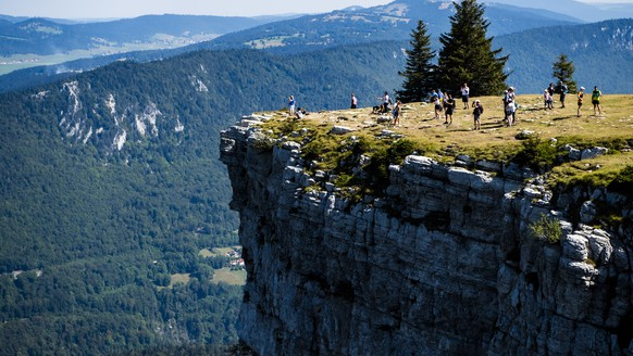 epaselect epa08591439 Tourists enjoy the beautiful weather and the view on the rim of the Creux-du-Van, Switzerland, 08 August 2020. The 'Creux du Van', a natural rock arena of immense proportions, is located at the border of the cantons of Neuenburg and Vaud. Impressive 160-meter-high vertical rock faces surround a four-kilometer-long and over one-kilometer wide valley basin.  EPA/JEAN-CHRISTOPHE BOTT