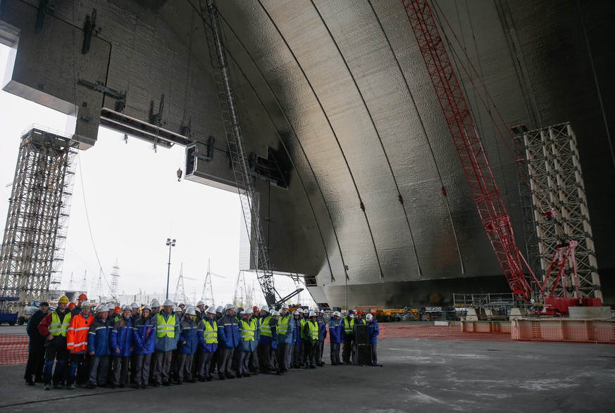 epa05278255 Workers of the Chernobyl nuclear power plant stand during the ceremony under the construction of a new protective shelter which will be placed over the remains of the nuclear reactor Unit 4, at Chernobyl nuclear power plant, in Chernobyl, Ukraine, 26 April 2016. In the early hours of 26 April 1986 the Unit 4 reactor at the Chernobyl power station blew apart. Facing nuclear disaster on unprecedented scale Soviet authorities tried to contain the situation by sending thousands of ill-equipped men into a radioactive maelstrom. The men barely lasted more than a few weeks suffering lingering painful deaths. The explosion of Unit 4 of the Chernobyl nuclear power plant is still regarded the biggest accident in the history of nuclear power generation. Ukrainians mark the 30th anniversary of Chernobyl's tragedy on 26 April 2016.  EPA/ROMAN PILIPEY