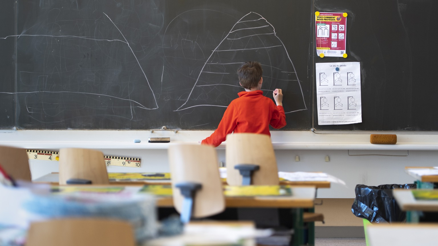 A child draws on the blackboard in an almost empty classroom as he attends a school childcare service at the school