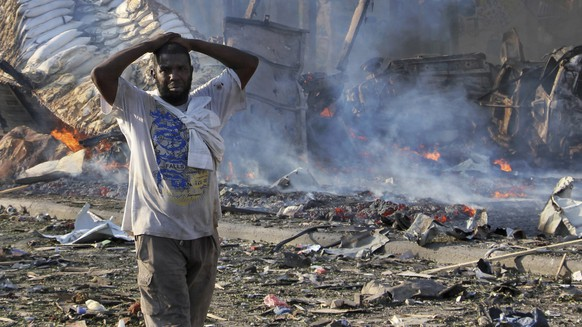 FILE -bIn this Saturday, Oct 14, 2017, file photo, a man walks past a dead body and destroyed buildings at the scene of a blast in the capital Mogadishu, Somalia. Somalia is marking the first anniversary of one of the world's deadliest attacks since 9/11, a truck bombing in the heart of Mogadishu that killed well over 500 people. The Oct. 14, 2017 attack was so devastating that the al-Shabab extremist group that often targets the capital never claimed responsibility amid the local outrage. As Somalis gather at a new memorial with a minute of silence, local media report that the man accused of orchestrating the bombing has been executed. (AP Photo/Farah Abdi Warsameh, File)