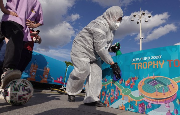 epa09225584 A cleaner works during the official EURO 2020 trophy tour at Gorky Park in Moscow, Russia, 24 May 2021. The UEFA EURO 2020 was postponed one year due to the ongoing coronavirus COVID-19 pandemic.  EPA/MAXIM SHIPENKOV