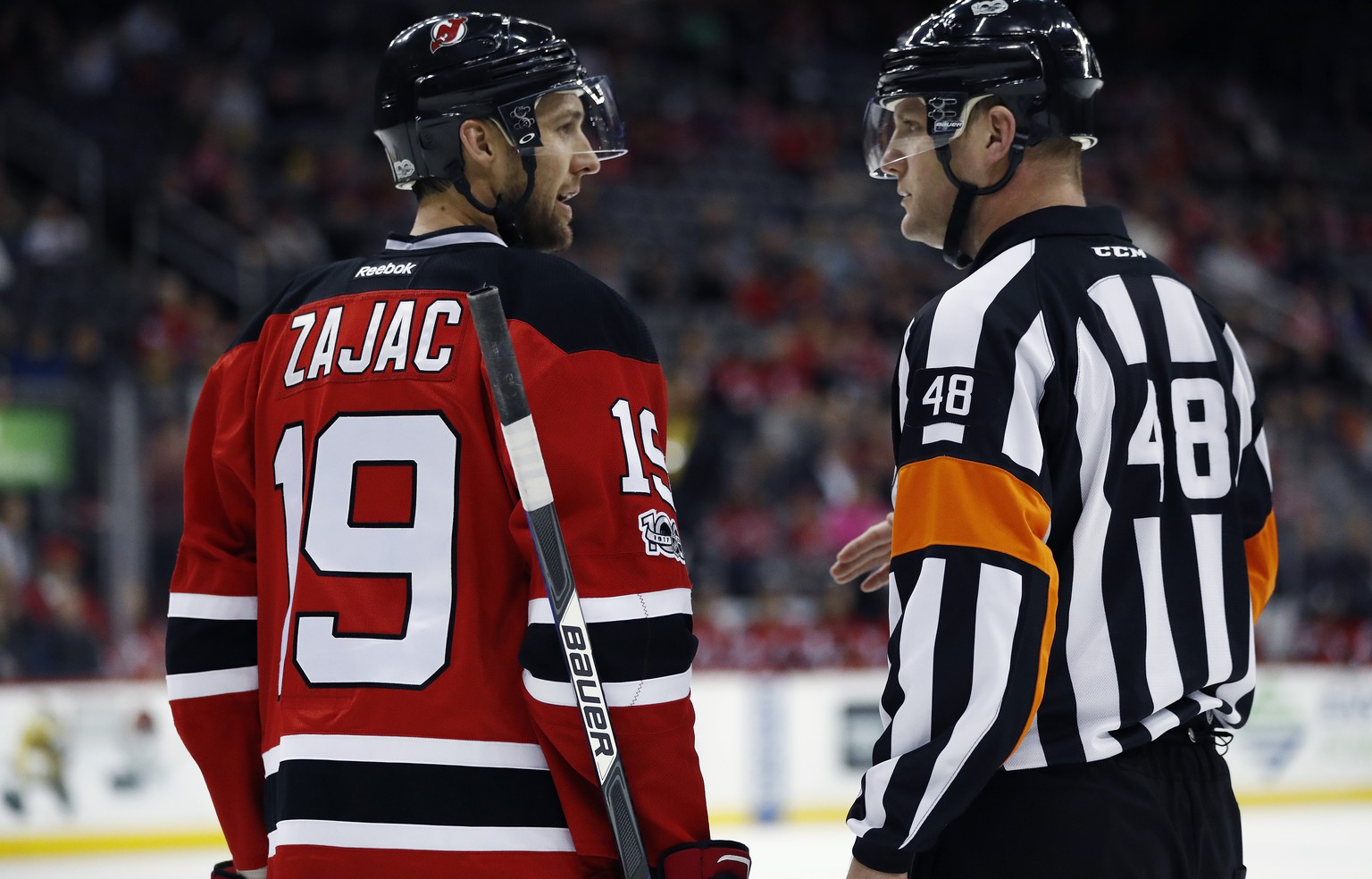 CORRECTS ID TO CHRIS SCHLENKER NOT GARRETT RANK FILE - This March 28, 2017, file photo shows New Jersey Devils center Travis Zajac, left,  talking to referee Chris Schlenker during the first period of an NHL game, in Newark, N.J. (AP Photo/Julio Cortez, File)
