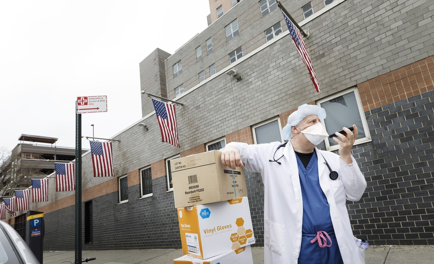 epa08333161 A doctor asks a colleague for help to bring  boxes of gloves and masks, donated by the areas Chinese community, inside Elmhurst Hospital Center in Queens, New York, USA, 30 March 2020. New York City is still the epicenter of the coronavirus outbreak in the United States and as 30 March there were reportedly 1,218 deaths related to COVID-19.  EPA/JUSTIN LANE