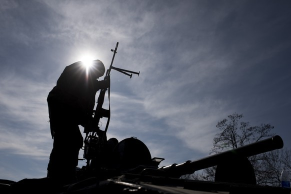 A Ukrainian soldier stands atop a military vehicle near Artemivsk, eastern Ukraine, Monday, Feb. 23, 2015. Ukraine delayed a promised pullback of heavy weapons from the front line Monday in eastern Ukraine, blaming continuing attacks from separatist rebels.  (AP Photo/Evgeniy Maloletka)