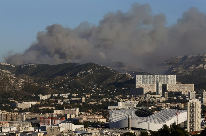 The Velodrome stadium in Marseille (front,R) is seen as smoke fills the sky during fires which burn the Calanques National Park, France, September 5, 2016. REUTERS/Jean-Paul Pelissier