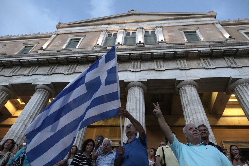 epa04807518 Protesters stand on the parliament holding Greek flags as they take part in a rally demanding that Greece remains in the Eurozone, in Athens, Greece, 18 June 2015. Eurozone finance ministers failed to find a breakthrough in the Greek bailout crisis, European Commission Vice President Valdis Dombrovskis said. 'No deal at Eurogroup,' he wrote on Twitter. 'Strong signal for Greece to engage seriously in negotiations.' Fears are mounting that cash-strapped Greece will soon go bankrupt. It is seeking to access 7.2 billion euros (8.2 billion dollars) remaining in its international bailout, but has been struggling for months to agree with its creditors on prerequisite economic reforms. EPA/YANNIS KOLESIDIS  EPA/YANNIS KOLESIDIS