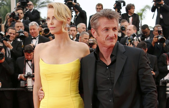Cast member Charlize Theron and actor Sean Penn pose on the red carpet as they arrive for the screening of the film