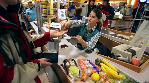 Eine Mann bezahlt am 20. Januar 2005 an einer Kasse im Migros Limmatplatz in Zuerich seine Einkaeufe. Migros zaehlt zu den groessten Anbietern in der Schweiz. Das Verkaufsnetz umfasst insgesamt 587 Standorte.  (KEYSTONE/Martin Ruetschi)    === ,  ===