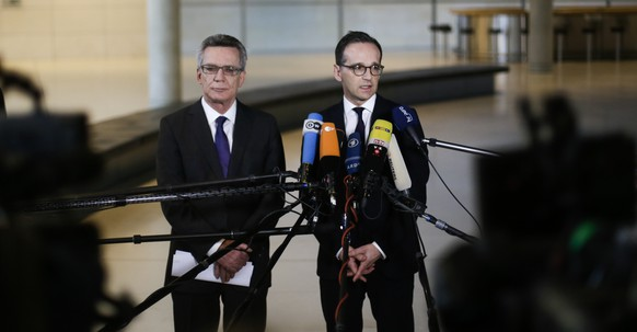 German Interior Minister Thomas de Maiziere, left, and Justice Minister Heiko Maas arrive for a statement on a planned reform of the laws on deportation and sexual offenses at the Reichstag Building, in Berlin, Germany, Tuesday, Jan. 12, 2016. (AP Photo/Markus Schreiber)