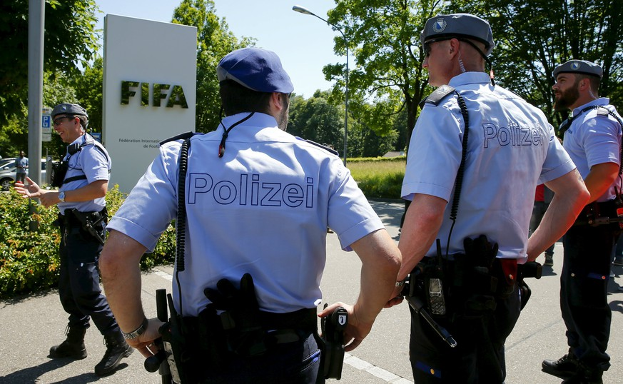 Swiss police officers stand in front of the entrance of the FIFA headquarters in Zurich, Switzerland, June 3, 2015. Interpol put two top former FIFA officials on its
