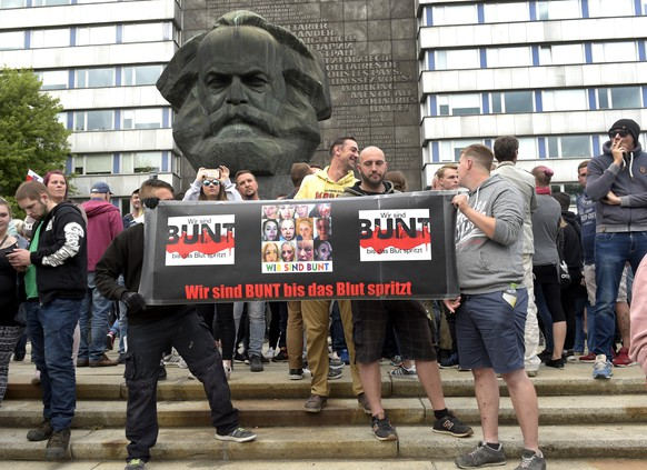 "Protesters gather for a far-right protest in front of a Karl Marx monument in Chemnitz, Germany, Monday, Aug. 27, 2018 after a man has died and two others were injured in an altercation between several people of ""various nationalities"" in the eastern German city of Chemnitz on Sunday. Slogan reads 'We Are Colorful Until Blood Splashes' (AP Photo/Jens Meyer)"