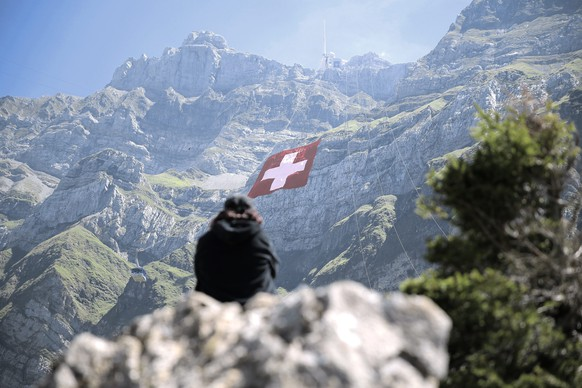 epa04868057 The world's largest Swiss flag is pictured at the ruggedly rock face of the mountain Saentis in Schwaegalp, eastern Switzerland, 31 July 2015.  The flag measures 80 meters to 80 meters and is the world's largest Swiss flag ever made. Saturday, 01 August, Switzerland is celebrating the national holiday.  EPA/PASCAL BLOCH