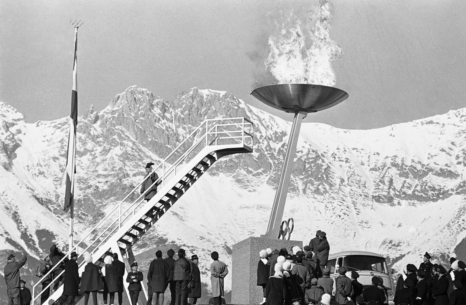 "Flames and smoke soar up with a ""whoosh"" as the Olympic flame is lit at the top of the Olympic Stadium at Innsbruck, Austria on Jan. 21, 1964. The lighting was part of the first rehearsal for the opening of the Winter Olympic Games on January 29. Some 1,300 high school students took part in the rehearsal at the Ski Jump Stadium, Imitating Athletes and marching behind the flags of the 35 nations entered in the competition. (AP Photo)"