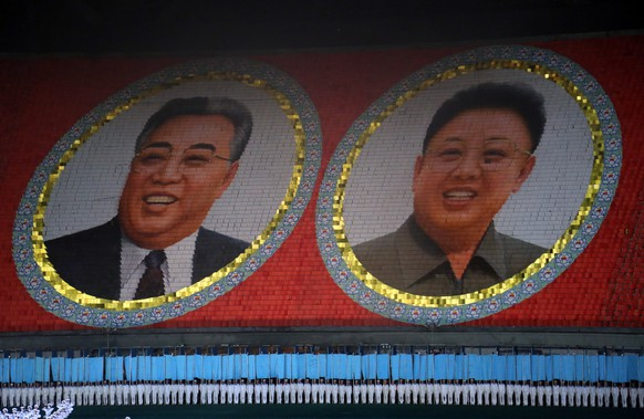 Portraits of the late North Korean leaders Kim Il Sung and Kim Jong Il are seen displayed as North Koreans participate in the