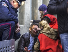 Women help treat a man injured when pro-Russian protesters stormed the offices of the state security services in Lugansk, eastern Ukraine April 6, 2014.  REUTERS/Stringer  (UKRAINE - Tags: POLITICS CIVIL UNREST)