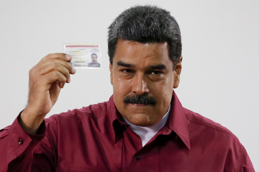 Venezuela's President Nicolas Maduro showed his ID after voting during presidential elections in Caracas, Venezuela, Sunday, May 20, 2018. Amidst hyperinflation and shortages of food and medicine Maduro is seeking a second six-year term in an election that a growing chorus of foreign governments refuse to recognize after key opponents were barred from running. (AP Photo/Ariana Cubillos)