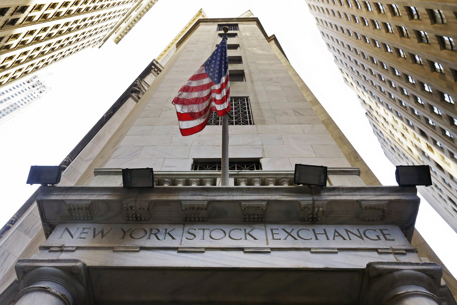In this Friday, Nov. 13, 2015, photo, the American flag flies above the Wall Street entrance to the New York Stock Exchange, in New York. U.S. stocks wobbled between small gains and losses Tuesday, Nov. 19, 2019, as investors paused following another record-setting day.  The major indexes have been steadily rising and setting records for weeks as a mix of solid economic data and corporate earnings inject confidence into the market. Worries about a potential recession have faded and investors are now closely watching for any developments in trade talks between the U.S. and China. (AP Photo/Richard Drew, File)