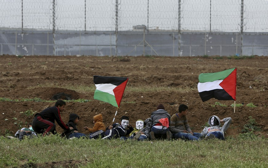 Protesters hid as they cover from teargas fired by Israeli troops near fence of Gaza Strip border with Israel, marking first anniversary of Gaza border protests east of Gaza City, Saturday, March 30, 2019. Tens of thousands of Palestinians on Saturday gathered at rallying points near the Israeli border to mark the first anniversary of weekly protests in the Gaza Strip, as Israeli troops fired tear gas and opened fire at small crowds of activists who approached the border fence.  (AP Photo/Adel Hana)