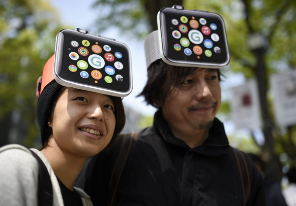 epa04718450 Apple products fans Makoto Saito (L) and her friend Kazumi Oda smile before entering a Japanese telecommunication store to purchase the wearable device in Tokyo, Japan, 24 April 2015. The Apple Watch, Apple's first new product category since 2010's iPad, goes on sale in eight countries from 24 April and will be sold by Apple only in its online store through at least May.  EPA/FRANCK ROBICHON
