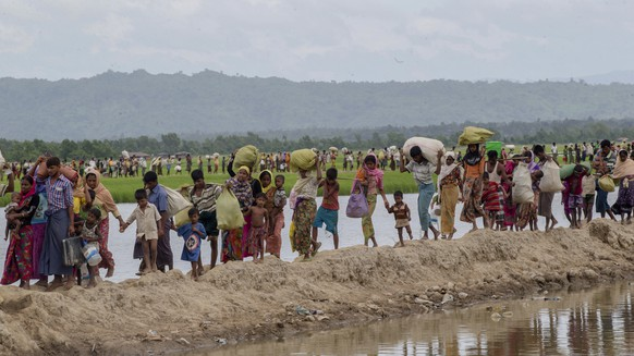 Rohingya Muslims, who spent four days in the open after crossing over from Myanmar into Bangladesh, carry their belongings after they were allowed to proceed towards a refugee camp, at Palong Khali, Bangladesh, Thursday, Oct. 19, 2017. More than 580,000 refugees have arrived in Bangladesh since Aug. 25, when Myanmar security forces began a scorched-earth campaign against Rohingya villages. Myanmar's government has said it was responding to attacks by Muslim insurgents, but the United Nations and others have said the response was disproportionate. (AP Photo/Dar Yasin)