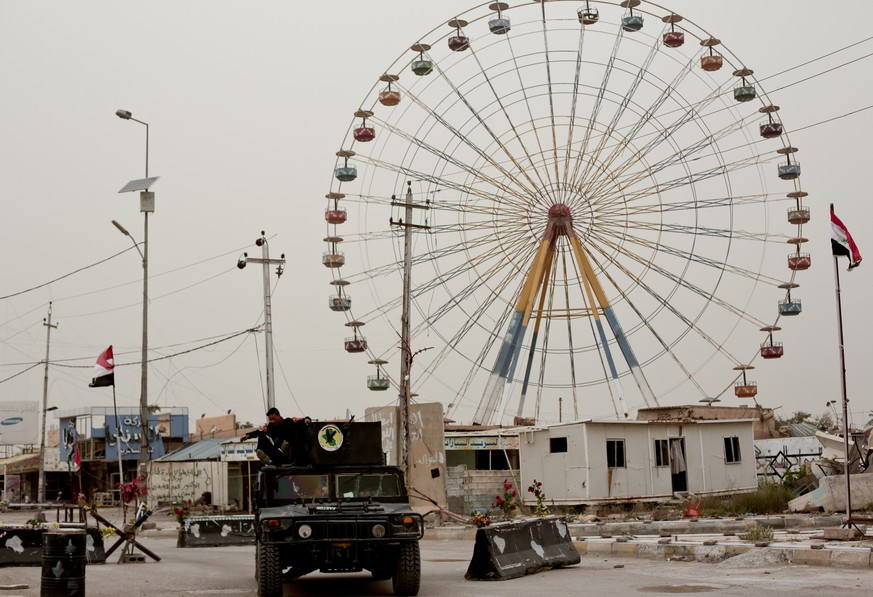 Iraqi counterterrorism forces drive past a ferris wheel in a central district of Ramadi on March 20, 2016. Months after being wrested from the control of the Islamic State group, Ramadi remains devastated with no running water or electricity, entire residential blocks destroyed and no clear picture on when or how it can be rebuilt. (AP Photo/Maya Alleruzzo)