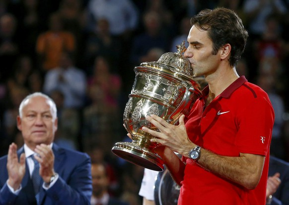 Tournament director Roger Brennwald (L) applaudes as Switzerland's Roger Federer kisses the trophy after winning his final match against Belgium's David Goffin at the Swiss Indoors ATP tennis tournament in Basel October 26, 2014.   REUTERS/Arnd Wiegmann (SWITZERLAND  - Tags: SPORT TENNIS TPX IMAGES OF THE DAY)