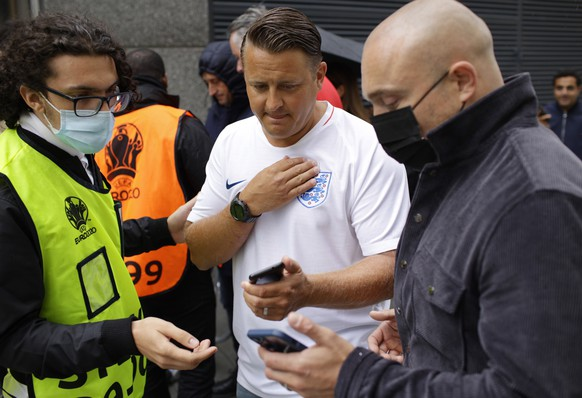 Stewards check for electronic tickets of fans as they enter Wembley Stadium in London, Sunday, July 11, 2021, prior to the Euro 2020 soccer championship final match between England and Italy. (AP Photo/David Cliff)