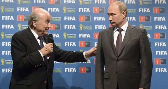 Russia's President Vladimir Putin (R) and FIFA President Sepp Blatter take part in the official hand over ceremony for the 2018 World Cup scheduled to take place in Russia, in Rio de Janeiro July 13, 2014. REUTERS/Alexey Nikolsky/RIA Novosti/Kremlin (BRAZIL - Tags: SPORT SOCCER WORLD CUP POLITICS) ATTENTION EDITORS - THIS PICTURE WAS PROVIDED BY A THIRD PARTY. REUTERS IS UNABLE TO INDEPENDENTLY VERIFY THE AUTHENTICITY, CONTENT, LOCATION OR DATE OF THIS IMAGE. FOR EDITORIAL USE ONLY. NOT FOR SALE FOR MARKETING OR ADVERTISING CAMPAIGNS. NO SALES. NO ARCHIVES. FOR EDITORIAL USE ONLY. NOT FOR SALE FOR MARKETING OR ADVERTISING CAMPAIGNS. THIS PICTURE IS DISTRIBUTED EXACTLY AS RECEIVED BY REUTERS, AS A SERVICE TO CLIENTS