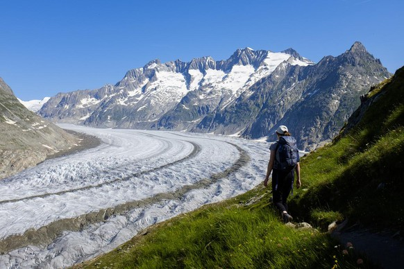 A woman walks next to the Swiss Aletsch Glacier during a beautiful summer day above Bettmeralp in Wallis, Switzerland, this Sunday, July 8, 2018. The Swiss Aletsch glacier, one of the largest ice streams in Europe, is the first Unesco World Heritage Site of the Alps. This huge river of ice that stretches over 23 km from its formation in the Jungfrau region (at 4000 m) down to the Massa Gorge in Wallis, around 2500 m below, fascinates and inspires every visitor. (KEYSTONE/Anthony Anex)