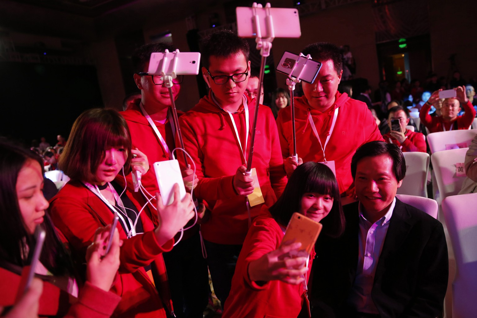 epa05226844 Fans of Xiaomi, pose and take photos with Lei Jun (R) , CEO of Chinese mobile internet company Xiaomi Technology Co. Ltd., before the Xiaomi product launch ceremony for the new Xiaomi 'Mi TV 3S' product  in Beijing City, China, 23 March 2016.  EPA/WU HONG