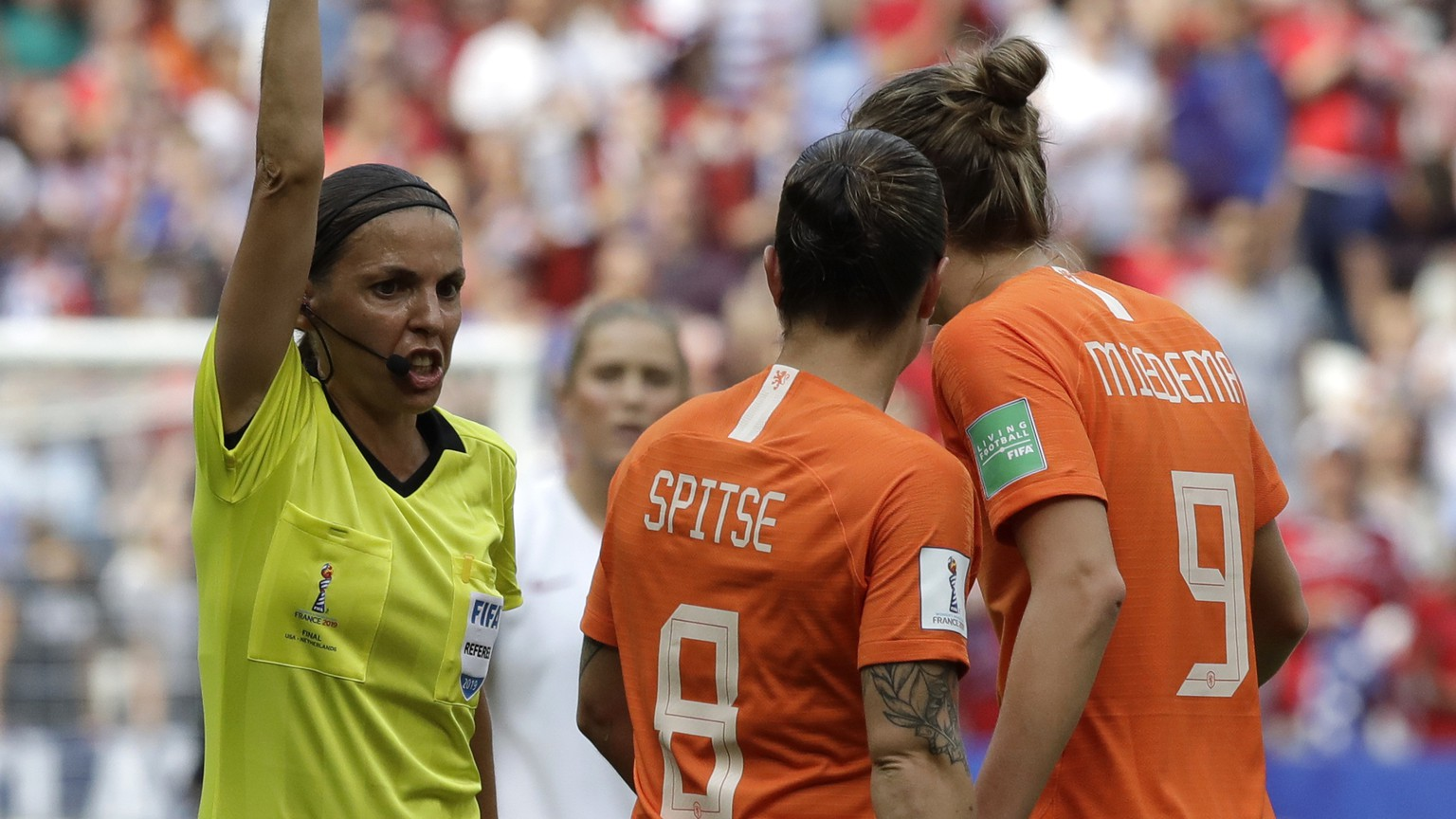Netherlands' Vivianne Miedema, right, talks to French referee Stephanie Frappart, left, as she shows a yellow card to Netherlands' Sherida Spitse, center, during the Women's World Cup final soccer match between US and The Netherlands at the Stade de Lyon in Decines, outside Lyon, France, Sunday, July 7, 2019. (AP Photo/Alessandra Tarantino)