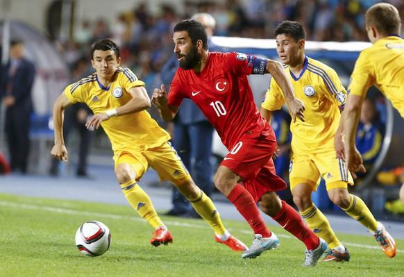 REFILE - CORRECTING ID OF TURKEY PLAYER   Turkey's Arda Turan (C), Kazakhstan's Ulan Konysbayev (L) and Bauyrzhan Islamkhan run for the ball during their Euro 2016 Group A qualifying soccer match at the Central Stadium in Almaty, Kazakhstan, June 12, 2015. REUTERS/Shamil Zhumatov