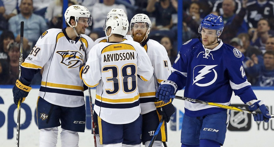 Tampa Bay Lightning's Jonathan Drouin, right, reacts as members of the Nashville Predators, including Roman Josi (59), of Finland, Viktor Arvidsson (38), of Sweden, and Ryan Ellis during the second period of an NHL hockey game Thursday, Jan. 5, 2017, in Tampa, Fla. (AP Photo/Mike Carlson)