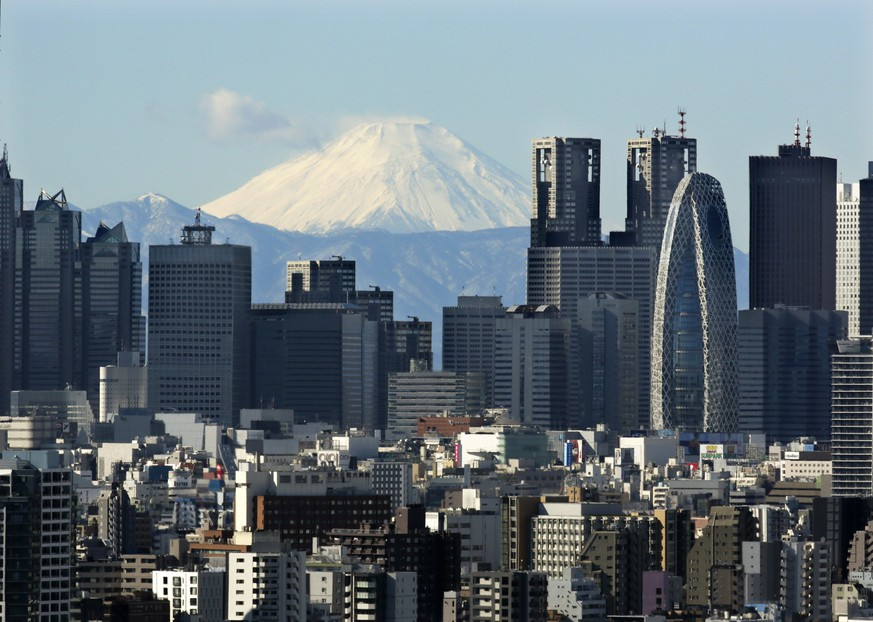 epa05112459 Snow-covered peak of Mount Fuji is seen through Shinjuku skyscrapers in Tokyo, Japan, 20 January 2016. Japan's parliament enacted on 20 Janaury 2016 the 3.32 trillion yen (about 28.2 billion US dollars) extra budget for 2015 fiscal year to bolster Japanese economy after approved by the Upper House.  EPA/KIMIMASA MAYAMA