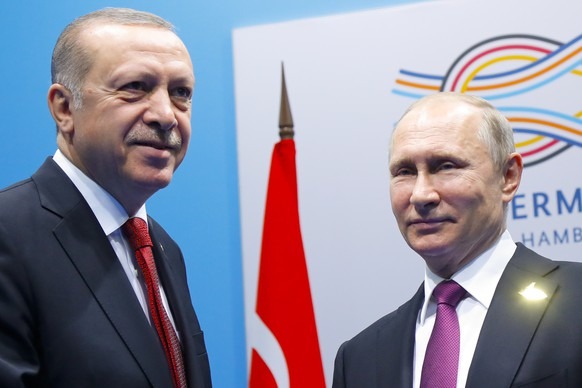 Russian President Vladimir Putin, right, and Turkish President Recep Tayyip Erdogan pose for a photo prior to their talks at the G-20 summit in Hamburg, northern Germany, Saturday, July 8, 2017. Putin and Erdogan underlined the importance of a Syria peace deal brokered by Russia and Turkey. (AP Photo/Alexander Zemlianichenko, Pool)