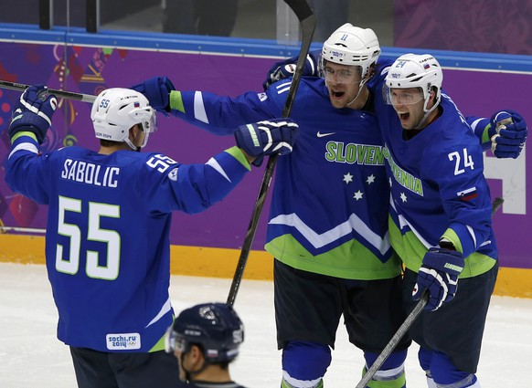 Slovenia's Rok Ticar (R) celebrates his goal against Slovakia with teammates Anze Kopitar (C) and Robert Sabolic during the third period of their men's preliminary round ice hockey game at the 2014 Sochi Winter Olympic Games, February 15, 2014.  REUTERS/Grigory Dukor (RUSSIA  - Tags: OLYMPICS SPORT ICE HOCKEY TPX IMAGES OF THE DAY)